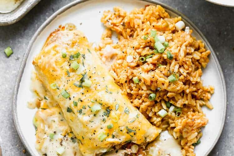 A plate with a smothered burrito and Mexican rice on it.