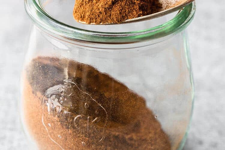 Homemade pumpkin pie spice in a clear glass jar with a spoon lifting some out.