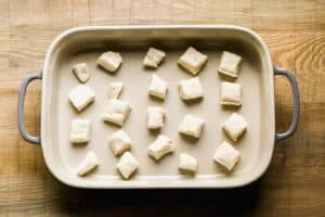 Pieces of biscuit dough placed in a casserole dish.