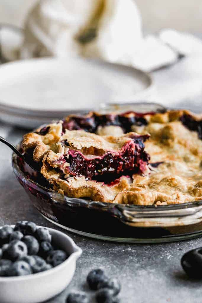 A slice of blueberry pie being removed from the pie dish by a spatula.
