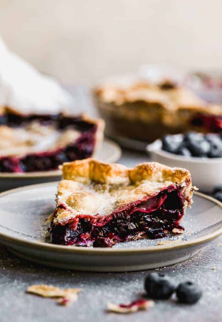 A slice of Blueberry Pie on a plate.