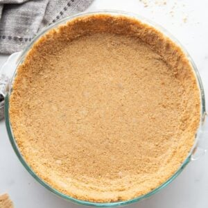 A homemade graham cracker pie crust in a clear glass pie dish.