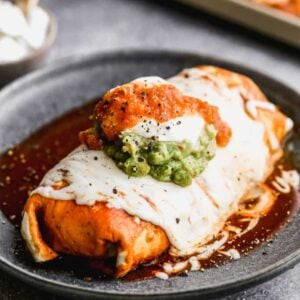 A wet burrito on a plate smothered in enchilada sauce and melted cheese.