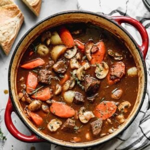 A large pot of beef stew with carrots, potatoes and mushrooms and sliced baguette on the side.