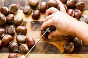 Slits being cut into the top of chestnuts, with a knife.