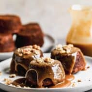 Three sticky toffee pudding cakes on a plate with sauce and crushed walnuts sprinkled on top.