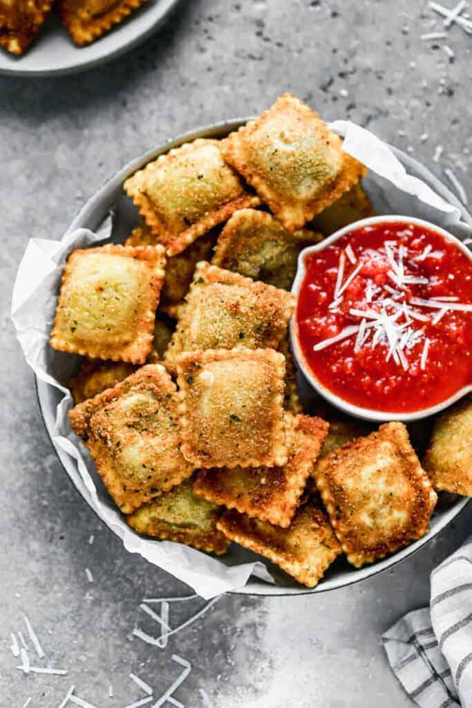 A bowl with toasted ravioli and a small bowl of marinara sauce.