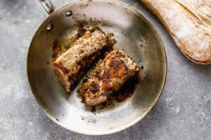 Pork tenderloin searing in a skillet.