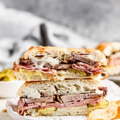 Two halves of a Cuban Sandwich stacked on a plate with chips on the side.