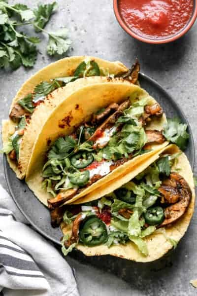 Three mushroom tacos on a plate, garnished with cilantro, hot sauce and sour cream.