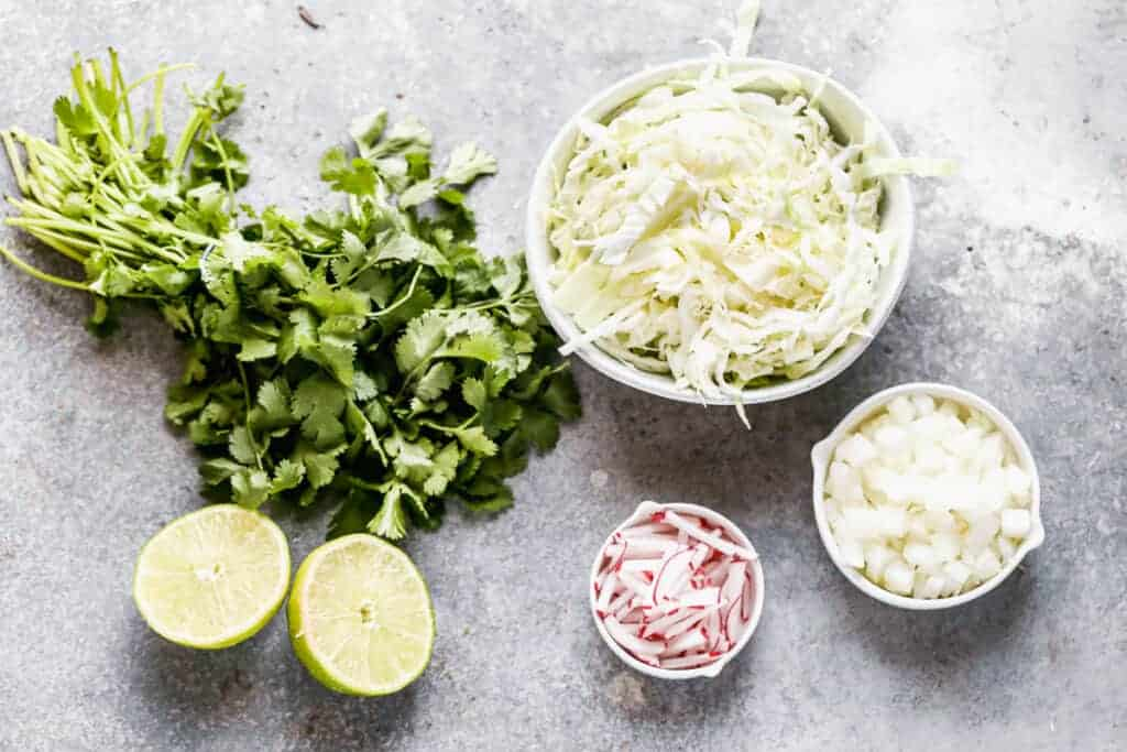 Toppings for pozole, including shredded cabbage, chopped onion, radishes, cilantro and limes.
