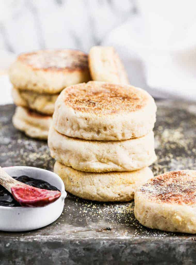 Three homemade English Muffins stacked on each other on a baking sheet.