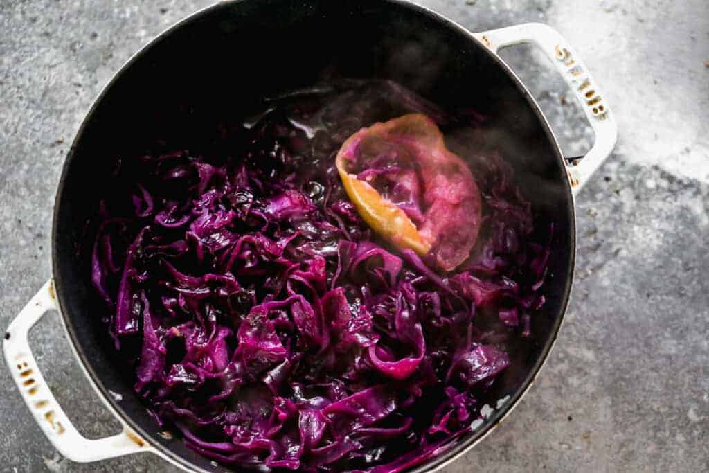 Boiled German red cabbage, in a pot, with a boiled apple.
