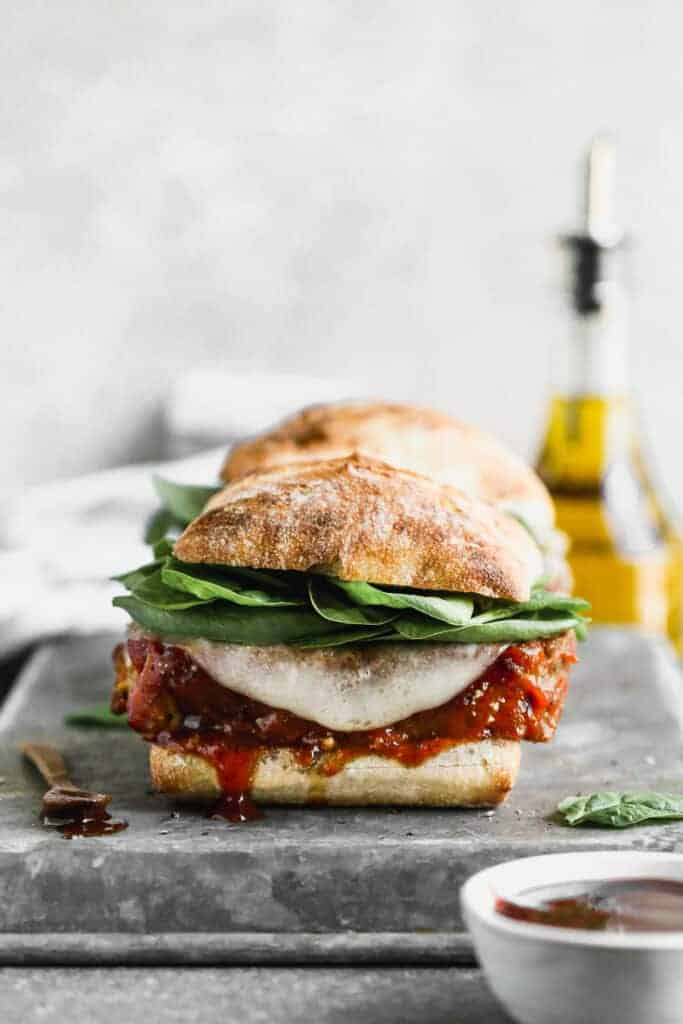 A Meatloaf Sandwich on a baking tray, ready to eat with toppings including cheese, meatloaf sauce and spinach.