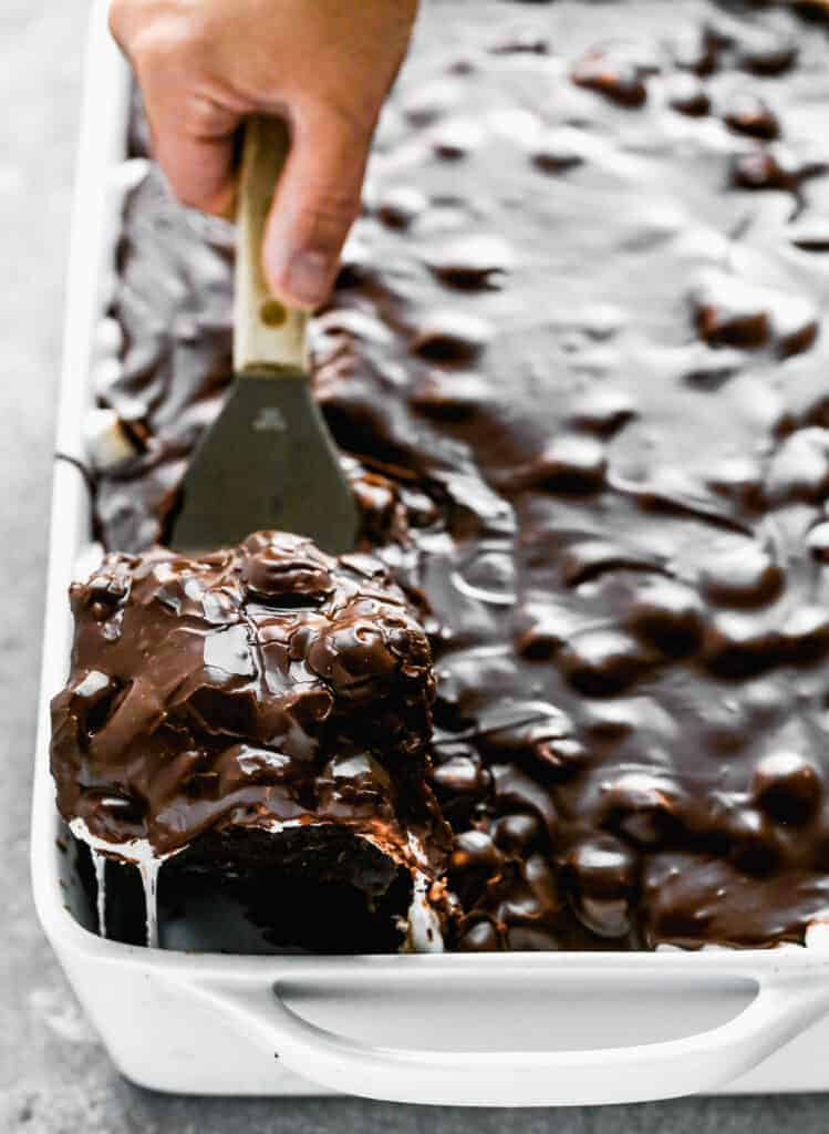 A pan of Mississippi Mud Cake with a spatula lifting out the first piece of cake.