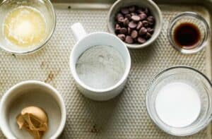 Flour in a mug surrounded by the ingredients needed to make peanut butter mug cake.