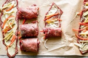 Rouladen rolls of thinly sliced round roast topped with matchstick carrots, onion, pickles and mustard, being rolled up.