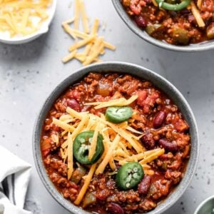 A bowl of Spicy Chili garnished with jalapeños and shredded cheddar cheese.