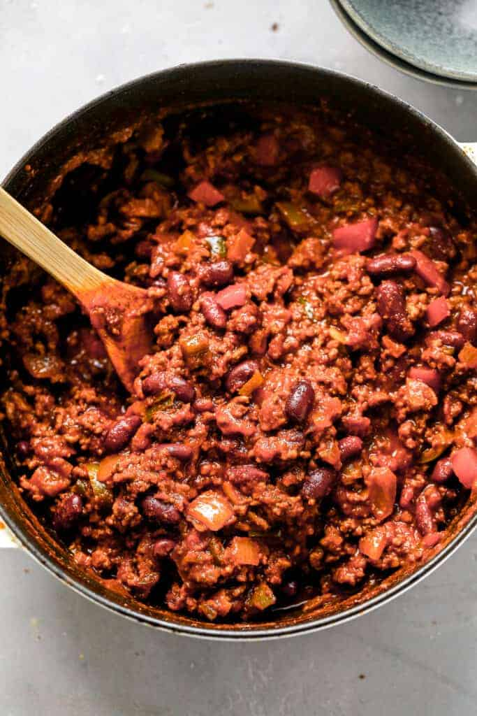 A pot full of cooked Spicy Chili, with a wooden spoon in it, ready to serve.