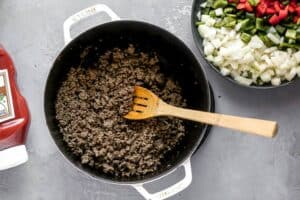 A pot with cooked ground beef and a wooden spoon in it.