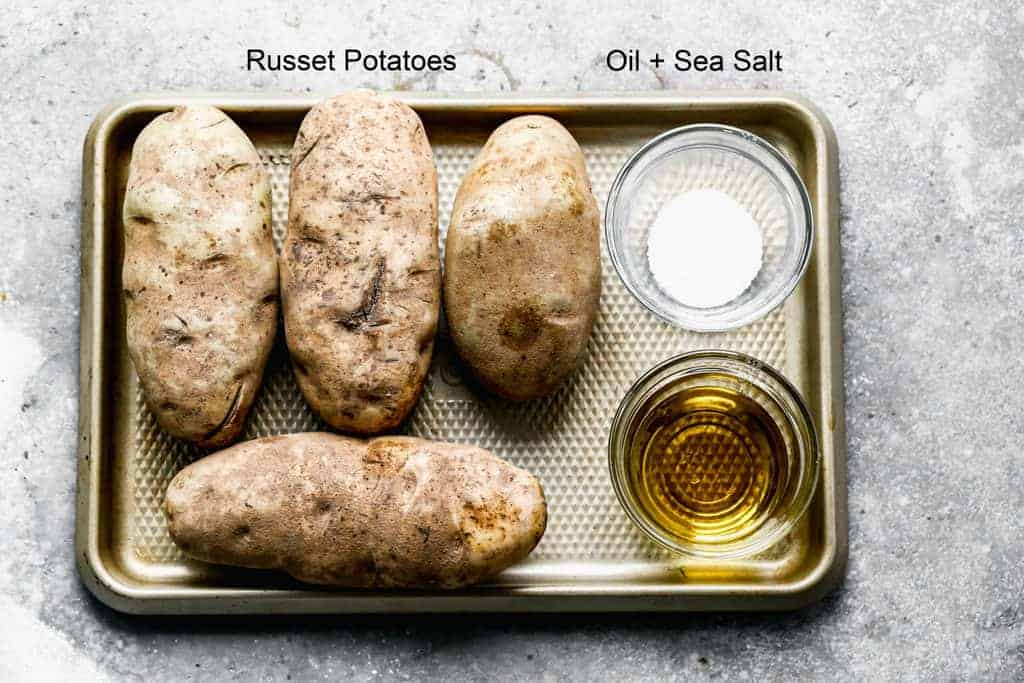 A baking tray with the ingredients needed to make Air Fryer Baked Potatoes including four russet potatoes and bowls of salt and oil.