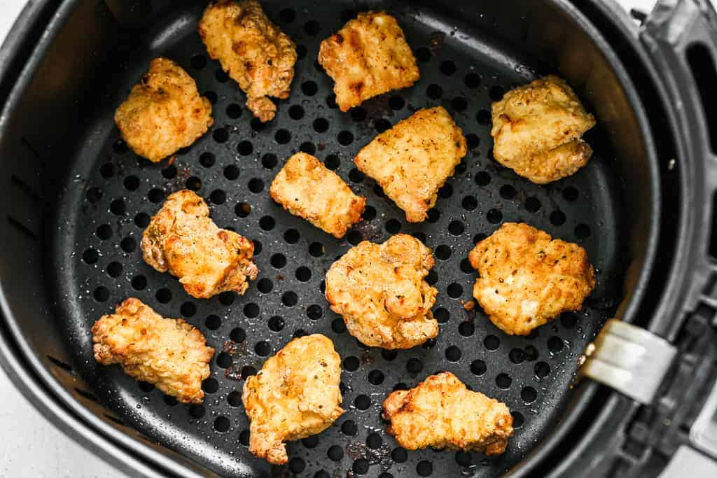 An air fryer basket with chicken nuggets inside.