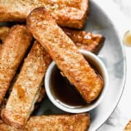 A plate with Air Fryer French Toast and a small container of syrup.