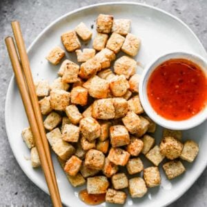 A plate with Air Fryer Tofu and sauce drizzled on top.