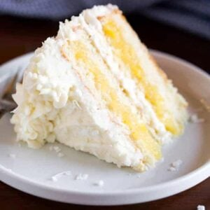 A slice of Coconut Cake on a plate, with layers of pineapple filling and frosted with coconut cream cheese frosting.
