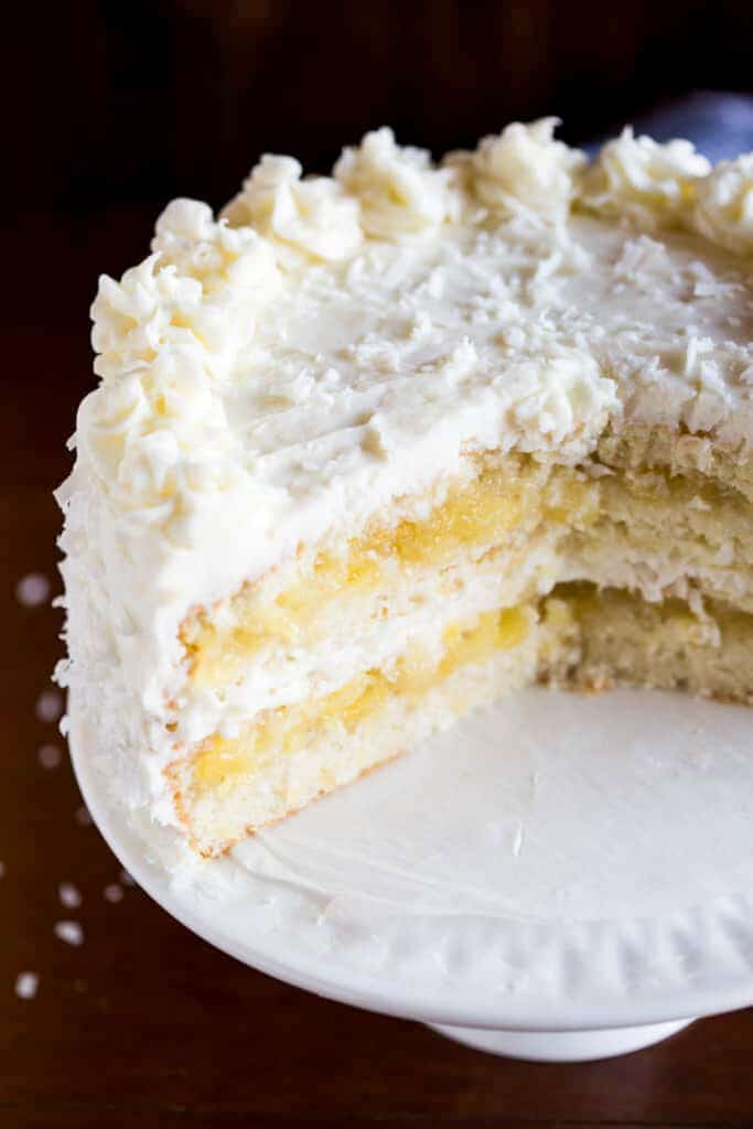 A whole coconut cake served on a cake stand, with a few slices removed to show the layers of cake and coconut frosting inside the cake.