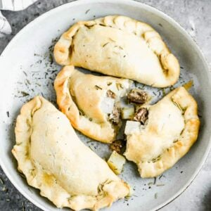 Cornish Pasties served on a plate with one cut in half to show the meat and potato filling inside.