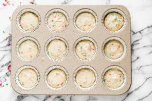 A cupcake pan with cupcake batter filling each cupcake liner.