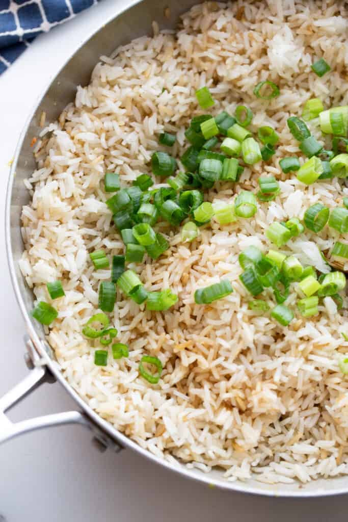 A skillet with fried rice and green onions on top.