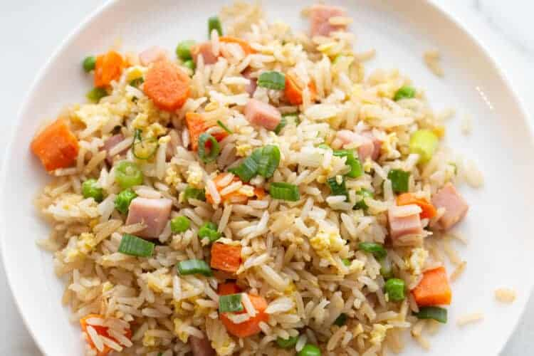 Ham fried rice with peas, carrots and ham, served on a white plate.