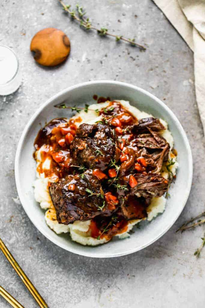 Instant pot short ribs served over mashed potatoes, on a plate.