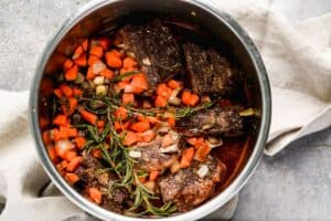 Beef short ribs, carrots, onion, herbs and liquid added to an instant pot and ready to pressure to cook.