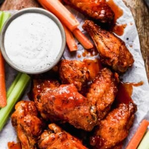 Air Fryer Chicken Wings on a wood board with ranch and veggies.