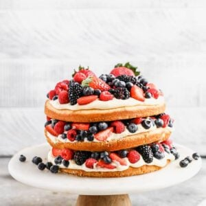 A three layer Berry Cake served on a cake stand.