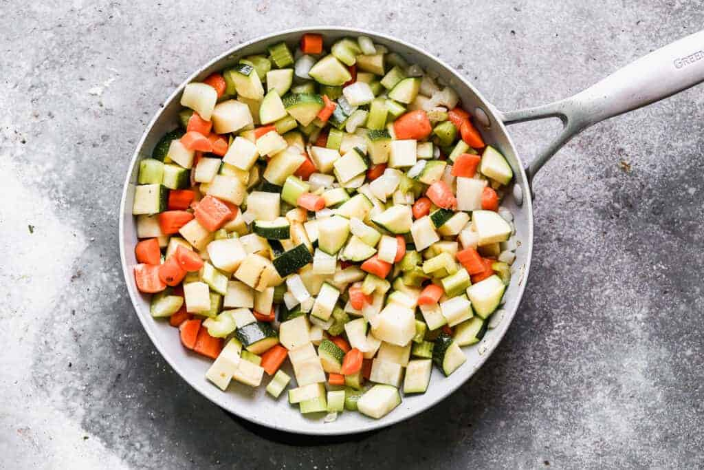 Chopped carrot, potato, celery, onion and zucchini sautéing in a skillet.