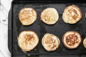 Ricotta pancakes cooking on a greased griddle.