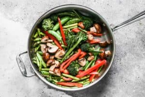 Vegetables sautéing in a skillet.