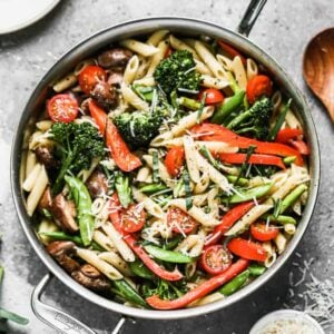 Pasta Primavera made with penne pasta and sautéed vegetables, cooking in a large skillet.