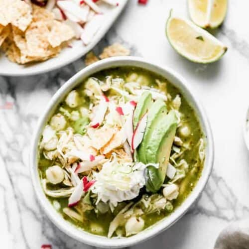 A bowl of Pozole Verde made with chicken, served with sliced avocado, cabbage and radishes, for garnish.