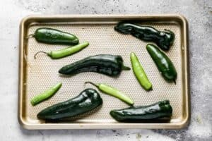Serrano and jalapeño peppers on a baking tray, ready to be roasted.