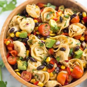 A bowl of Tortellini Pasta Salad with beans, corn, avocado and dressing.