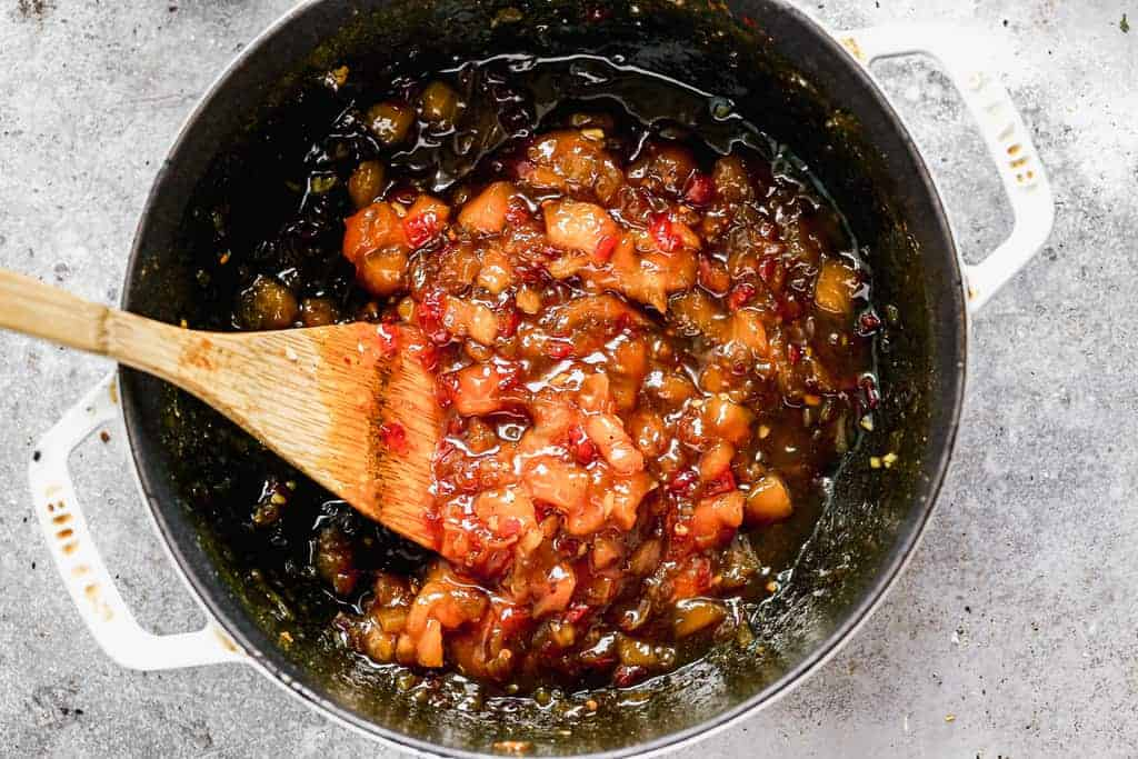 Mango Chutney cooking a large skillet, with a wooden spoon.