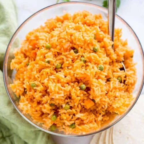 Mexican Rice with peas and carrots, served in a large bowl, with a spoon.