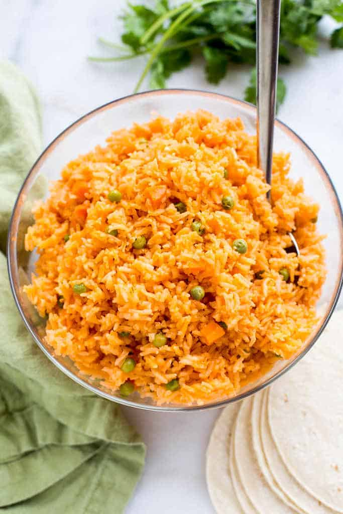 Authentic Mexican rice with carrots and peas, served in a bowl.
