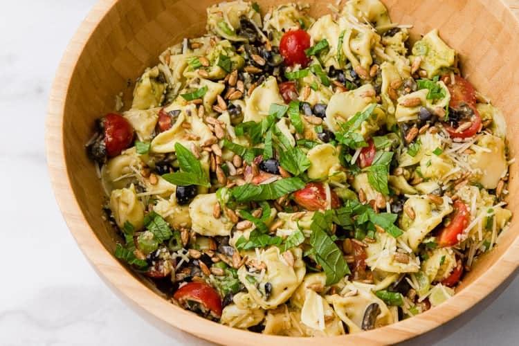 Pesto Tortellini tossed in a bowl.