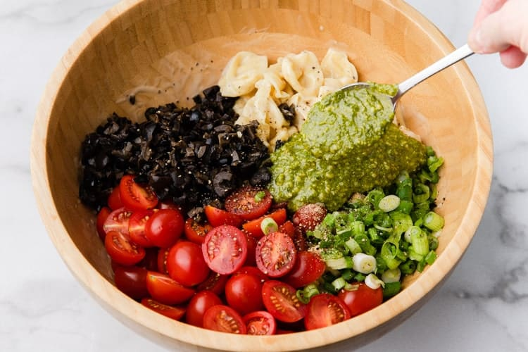 Cooked tortellini, pesto sauce, olives, tomatoes and green onion added to a bowl.
